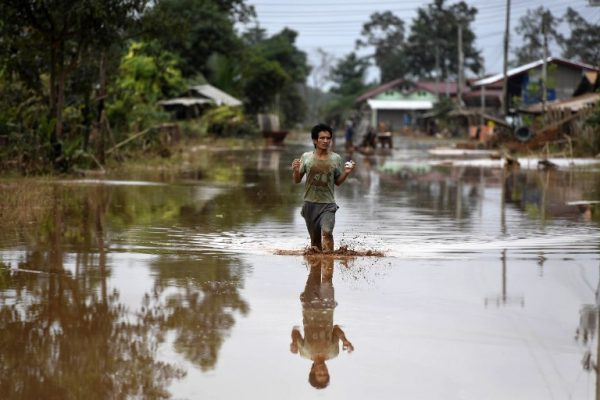 A man wades through a flooded road at a village in Sanamxai, Attapeu province, on July 26, 2018. Rescuers battled fresh rains on July 26 to reach scores of people still missing after a dam collapse in southern Laos that unleashed a torrent of water, washing away whole villages and killing at least 26 people. / AFP PHOTO / NHAC NGUYEN