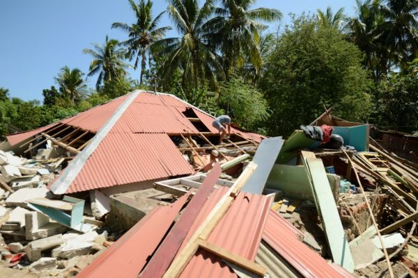 A man walks over the roof of a collapsed house at Pemenang village in northern Lombok in West Nusa Tenggara province on August 7, 2018, two days after the area was struck by an earthquake. The shallow 6.9-magnitude quake killed at least 105 people and destroyed thousands of buildings in Lombok on August 5, just days after another deadly tremor surged through the holiday island and killed 17. / AFP PHOTO / SONNY TUMBELAKA